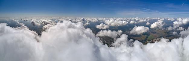 Luftaufnahme vom flugzeugfenster in großer höhe der erde bedeckt mit geschwollenen kumuluswolken, die sich vor dem regen bilden.