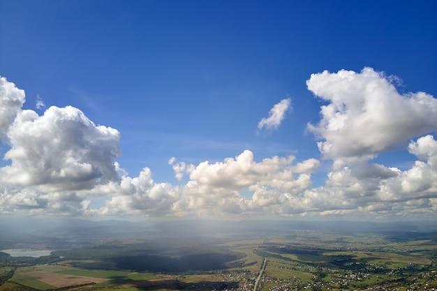 Luftaufnahme vom flugzeugfenster in großer höhe der erde bedeckt mit weißen geschwollenen kumuluswolken.