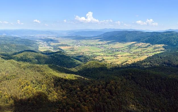 Luftaufnahme von berghügeln, die an einem hellen sommertag mit dichten grünen wäldern bedeckt sind.
