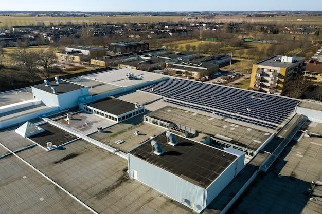 Luftaufnahme von blauen photovoltaik-sonnenkollektoren, die auf dem dach eines industriegebäudes montiert sind, um grünen ökostrom zu produzieren. erstellung eines nachhaltigen energiekonzepts.