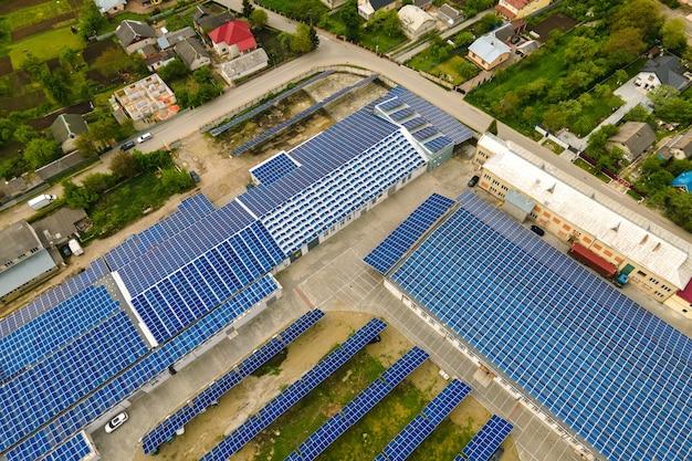 Luftaufnahme von blauen photovoltaik-sonnenkollektoren, die auf dem dach eines industriegebäudes montiert sind, um sauberen ökologischen strom zu erzeugen. produktion eines erneuerbaren energiekonzepts.