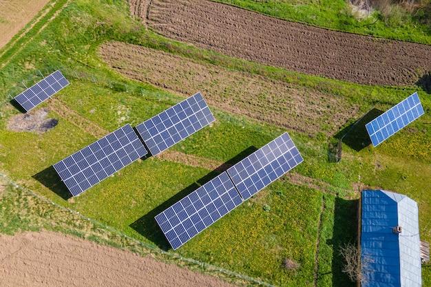 Luftaufnahme von blauen photovoltaik-sonnenkollektoren, die auf hinterhofboden montiert sind, um sauberen ökologischen strom zu erzeugen. produktion eines erneuerbaren energiekonzepts.