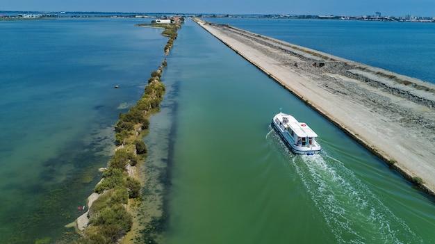 Luftaufnahme von booten im kanal in der lagune des mittelmeers etang de thau wasser von oben, reisen mit dem lastkahn in südfrankreich