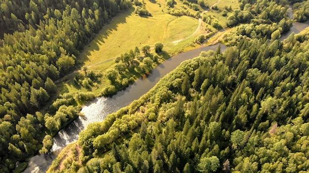 Luftaufnahme von der drohne über den kurvenfluss, die wiese, den wald und den bodenweg. top naturlandschaft