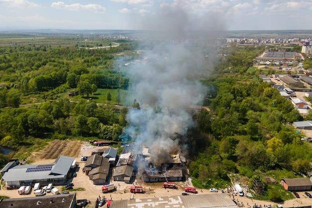 Luftaufnahme von feuerwehrleuten, die ein zerstörtes gebäude in brand mit eingestürztem dach und aufsteigendem dunklem rauch löschen.