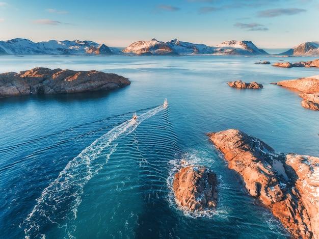 Luftaufnahme von fischerbooten, felsen im blauen meer, schneebedeckten bergen und buntem himmel mit wolken bei sonnenuntergang