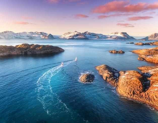 Luftaufnahme von fischerbooten, felsen im blauen meer, schneebedeckten bergen und buntem lila himmel mit roten wolken bei sonnenuntergang