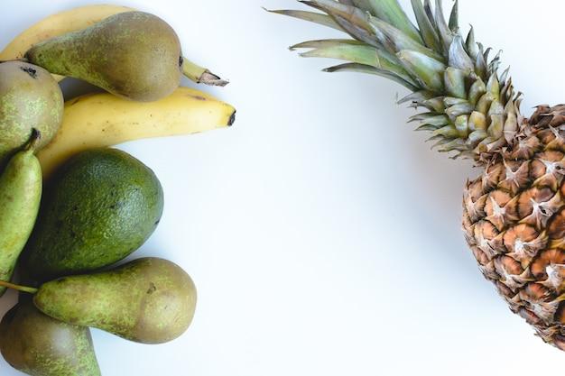 Luftaufnahme von frischen bananen, birnen, avocados und ananas auf einem weißen hintergrund