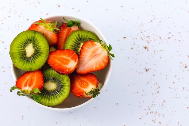 Luftaufnahme von geschnittenen erdbeeren und kiwis in einer weißen schüssel auf weiß mit braunem zucker
