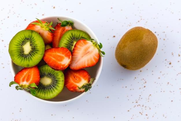 Luftaufnahme von geschnittenen erdbeeren und kiwis in einer weißen schüssel auf weißer und einer ganzen geflügelten kiwi