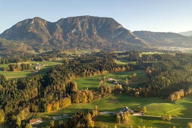 Luftaufnahme von grünen wiesen mit dörfern und wald in österreichischen alpenbergen.