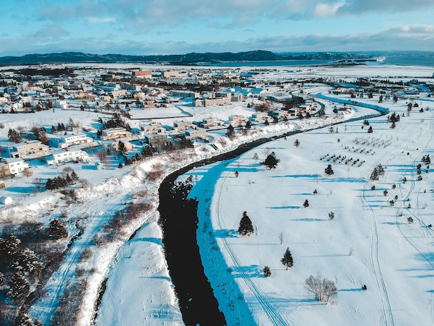 Luftaufnahme von häusern, feldern und bäumen, die mit schnee unter blauem und weißem himmel bedeckt sind