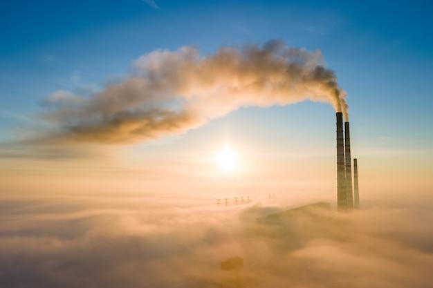 Luftaufnahme von hohen rohren des kohlekraftwerks mit schwarzem rauch, der bei sonnenaufgang die umweltverschmutzende atmosphäre aufsteigt.