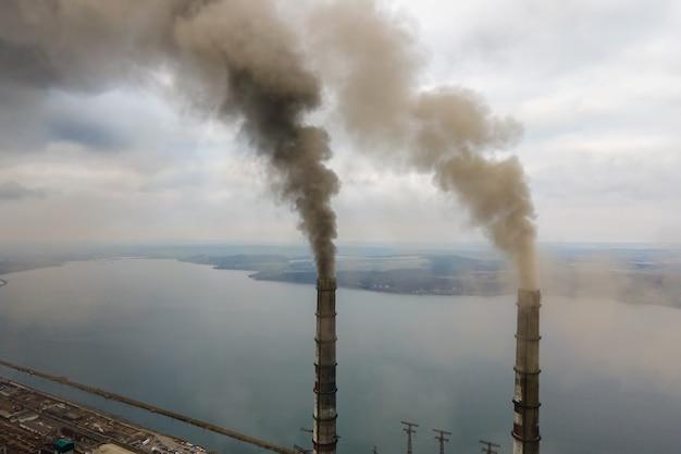 Luftaufnahme von hohen rohren des kohlekraftwerks mit schwarzem rauch, der die umweltverschmutzende atmosphäre nach oben bewegt.