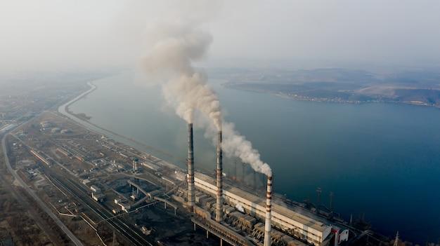 Luftaufnahme von hohen schornsteinrohren mit grauem rauch aus kohlekraftwerk. stromerzeugung mit fossilen brennstoffen.