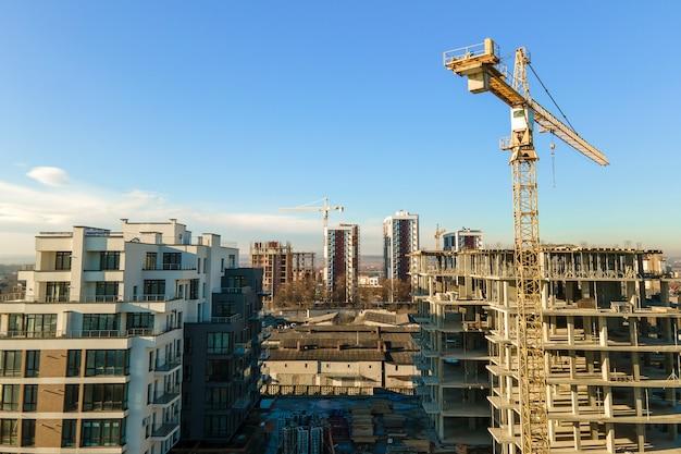 Luftaufnahme von hohen turmdrehkranen und wohngebäuden im bau. immobilien-entwicklung.