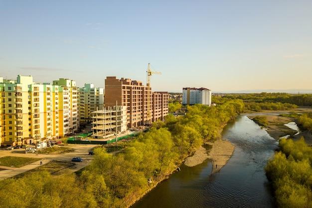 Luftaufnahme von hohen wohngebäuden im bau und bystrytsia-fluss in der stadt ivanofrankivsk, ukraine.