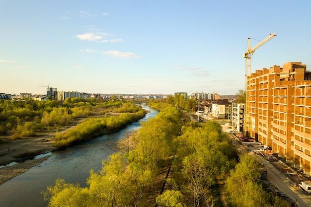 Luftaufnahme von hohen wohnwohngebäuden im bau und bystrytsia-fluss in der stadt iwano-frankiwsk, ukraine.