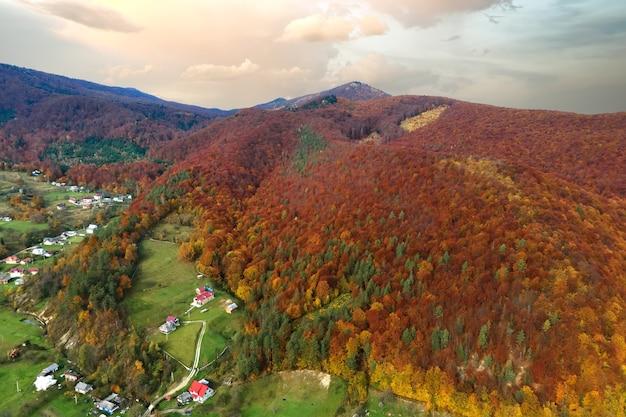 Luftaufnahme von kleinen hirtenhäusern auf breiter wiese zwischen herbstwald autumn