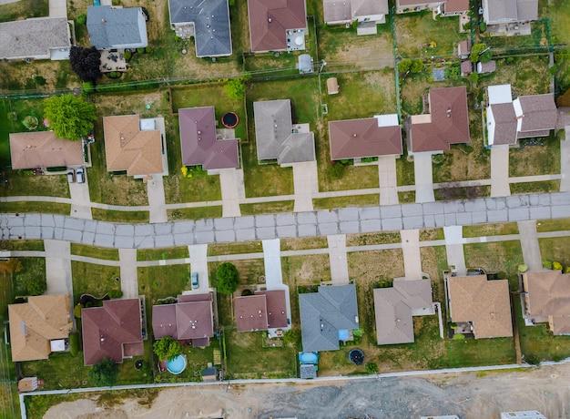 Luftaufnahme von kleinen stadthäusern auf der straße in der landschaft von oben über dem wohngebiet