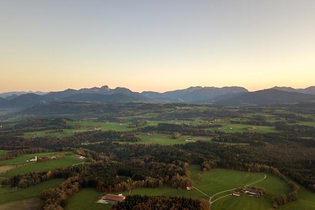 Luftaufnahme von kleinen verstreuten bauernhäusern mit roten ziegeldächern zwischen grünen ackerfeldern und entferntem bergwald im sommer.