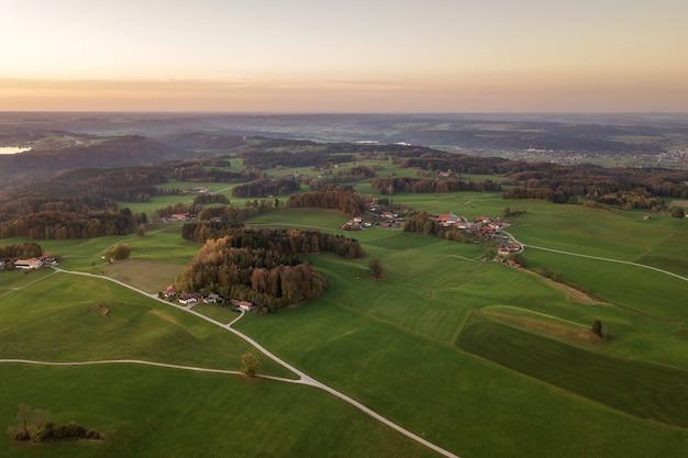 Luftaufnahme von kleinen verstreuten bauernhäusern mit roten ziegeldächern zwischen grünen bauernfeldern und entferntem bergwald im sommer.