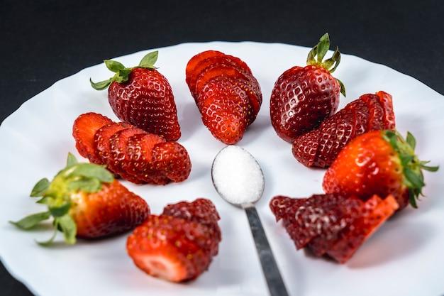 Luftaufnahme von natürlichen erdbeeren auf einem weißen teller mit einem löffel zucker auf schwarz