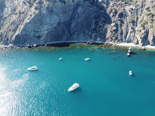 Luftaufnahme von oben auf azurblauem meer und felsigen ufern kleine wellen auf kristallklarer wasseroberfläche in