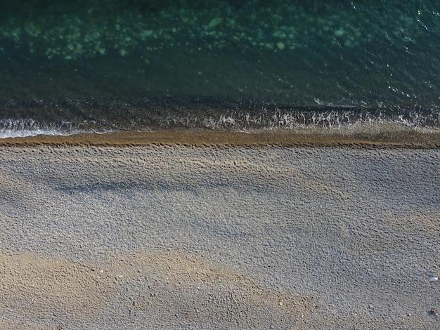 Luftaufnahme von oben auf azurblauem meer und kieselstrand kleine wellen auf kristallklarer wasseroberfläche in