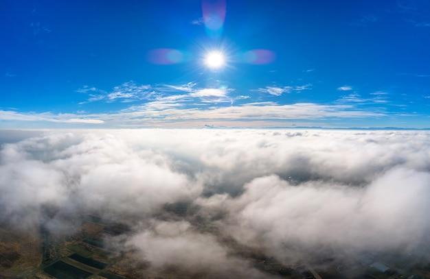 Luftaufnahme von oben auf weiße geschwollene wolken an einem sonnigen tag.