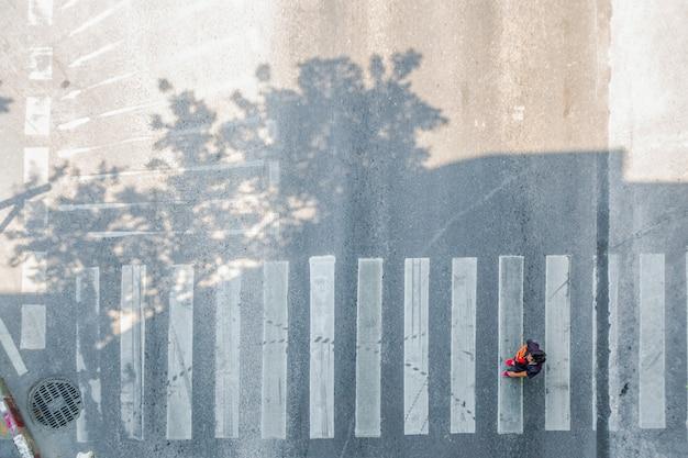 Luftaufnahme von oben bewegung des zebrastreifens oder zebrastreifens von personen. füße der fußgänger, die auf der stadtstraße überqueren.