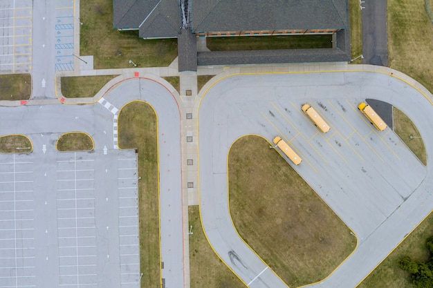 Luftaufnahme von oben die gelben schulbusse, die in der nähe der high school geparkt sind