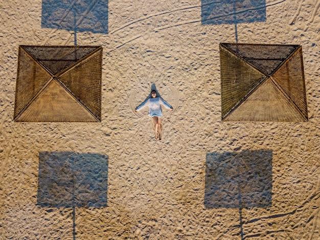 Luftaufnahme von oben eines schönen mädchens liegt auf dem sand zwischen sonnenschirmen. das mädchen am strand in einem kleid am meer.