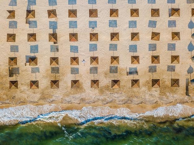 Luftaufnahme von oben eines schönen mädchens liegt auf dem sand zwischen sonnenschirmen