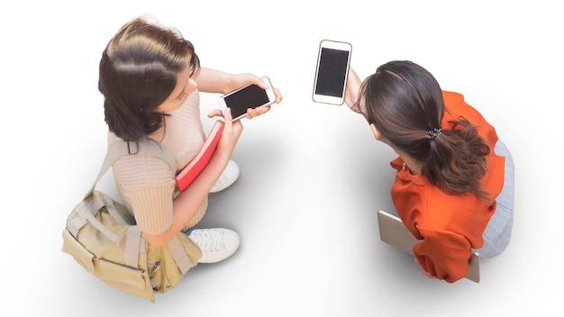 Luftaufnahme von oben mit zwei studentinnen mit smartphone-stand an der weißen bürgersteigstraße