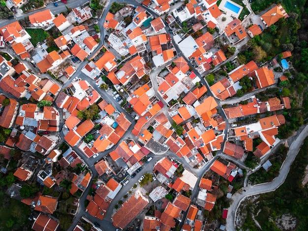 Luftaufnahme von oben nach unten auf roten dächern von häusern in einem kleinen dorf.
