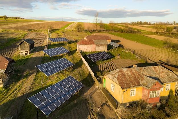 Luftaufnahme von oben nach unten auf sonnenkollektoren im grünen ländlichen dorfhof.