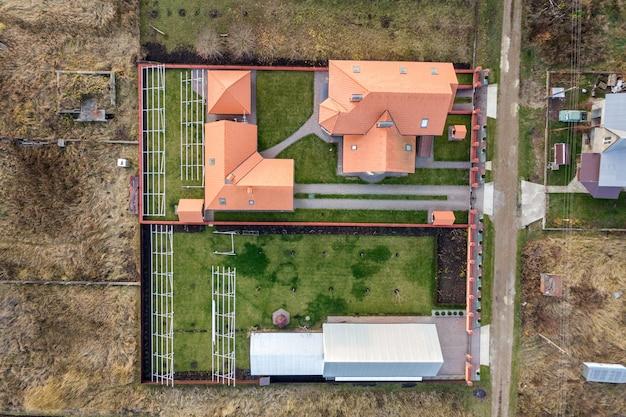 Luftaufnahme von oben nach unten eines privathauses mit rotem ziegeldach und rahmenkonstruktion für die installation von sonnenkollektoren.