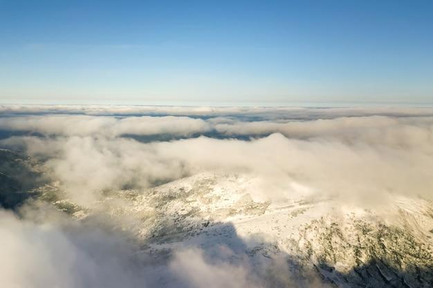 Luftaufnahme von oben von weißen geschwollenen wolken, die schneebedeckte berggipfel in hellem sonnigem tag bedecken.