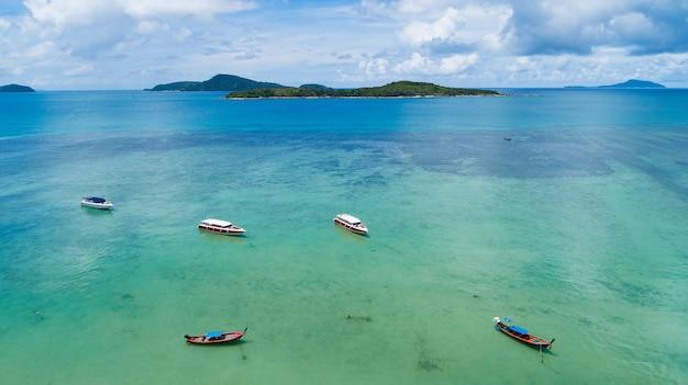 Luftaufnahme von thailändischen traditionellen longtail-fischerbooten, segelbooten, yachten im tropischen meer schöne inselküste in phuket, thailand.