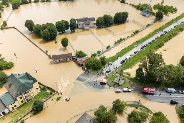 Luftaufnahme von überfluteten häusern und rettungsfahrzeugen, die leute in der stadt halych, westukraine retten.