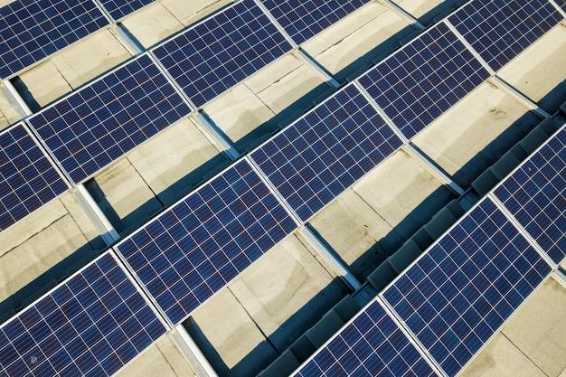 Luftaufnahme von vielen photovoltaik-sonnenkollektoren, die vom industriegebäudedach montiert werden.
