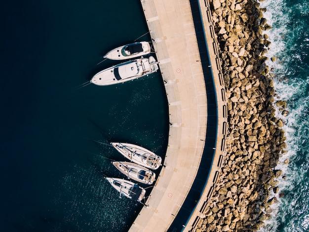 Luftaufnahme von weißen segelbooten, die an der küste des ozeans angedockt sind