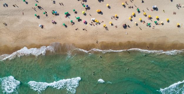 Luftaufnahme von wellen, die am ufer brechen. bunte sonnenschirme und leute, die den sommer genießen. brasilianischer strand.