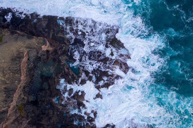 Luftaufnahme von wellen, die auf felsen krachen Kostenlose Fotos