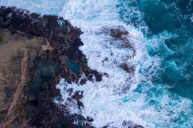 Luftaufnahme von wellen, die auf felsen krachen