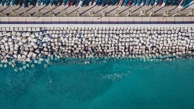 Luftaufnahme von zementwürfelblöcken, die das ufer vor den wellen im hafen in malaga schützen