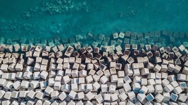 Luftaufnahme von zementwürfelblöcken, die das ufer vor den wellen im hafen von malaga, spanien schützen.