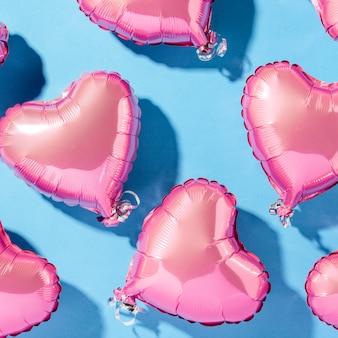Luftballonherzform auf einer blauen oberfläche. natürliches licht. banner. konzept liebe, hochzeit, foto zone. flachgelegt, draufsicht