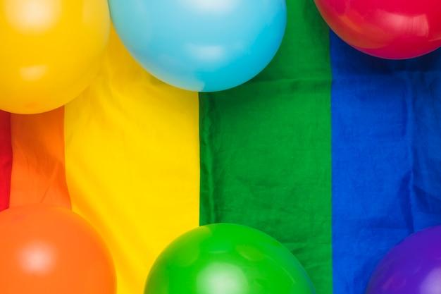 Luftballons auf gestreiften regenbogenfahne